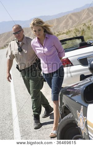 Full length of a traffic officer arresting young woman