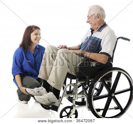 A senior man in a wheelchair and teen volunteer enjoying each other's company.  On a white background.