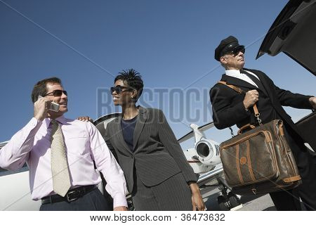Low angle view of happy multiethnic business couple standing with driver holding luggage at airfield