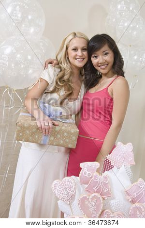 Portrait of a happy bride holding gift while standing with friend at party