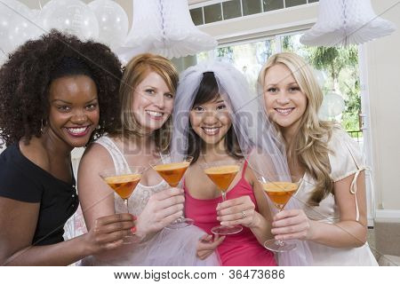 Portrait of happy multi ethnic friends holding cocktail glasses at party