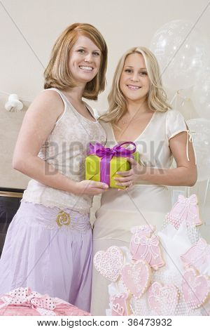 Portrait of happy bride and her friend holding gift box at party