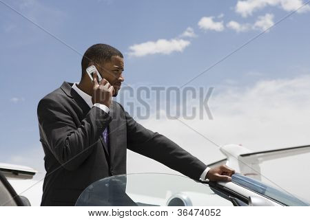 Young African American businessman on a call by car at airfield