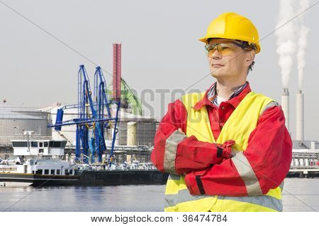 Engineer, wearing safety gear standing with his arms crossed and a confident, proud look on his face in front of an industrial harbor