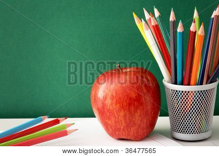 Close-up of colorful pencils with big red apple near by on background of blackboard