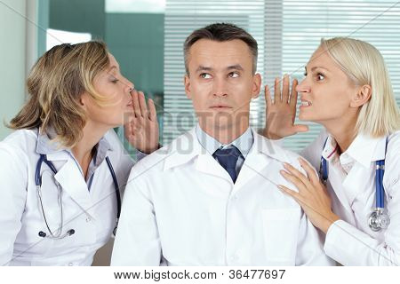 Portrait of pensive male clinician between two gossiping women