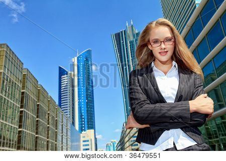 Smiling young business woman standing on the street of the big city.