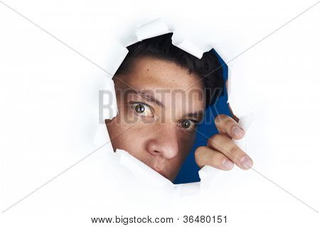 Young man looking through the hole in the white paper