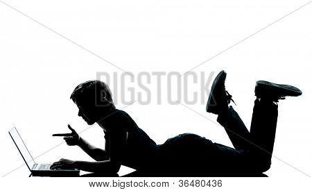 um jovem adolescente caucasiano silhueta menino menina computador computação portátil deitado na frente lengt completo