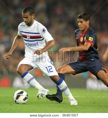 BARCELONA - AUG, 20: Fernando Tissone of UC Sampdoria vies with Jonathan Dos Santos of FC Barcelona during Joan Gamper Trophy match at Nou Camp Stadium in Barcelona, Spain. August 20, 2012
