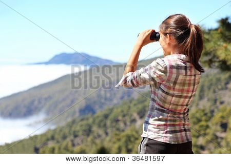 Hiker looking in binoculars enjoying view above clouds during hiking trip. Young Asian woman on hike on La Palma, Canary Islands, Spain.