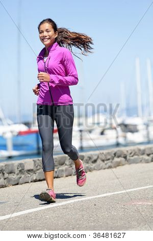 Woman running in fall / autumn running clothing outfit. Smiling happy female athlete runner training on waterfront harbour pier in San Francisco, California, USA. Mixed race fit fitness sport model.