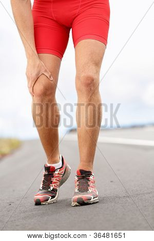 Knee pain - running sport injury. Male runner having knee problems during exercise outside.