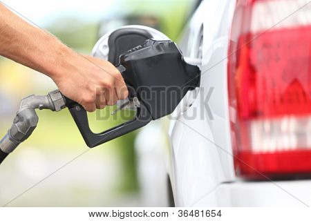Pumping gas at gas pump. Closeup of man pumping gasoline fuel in car at gas station.