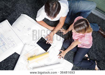 Vista de alto ângulo do casal sentado no tapete com plantas e digital tablet