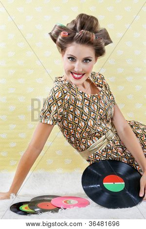 Portrait of young woman in a patterned dress wearing hair curlers while sitting with vinyl record