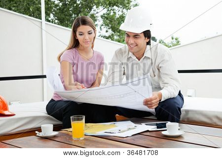Young male architect having a discussion about house plans with female