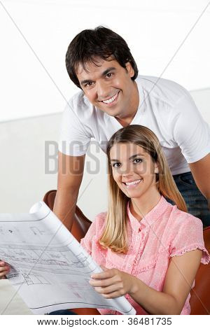 Portrait of young man smiling with woman holding blueprint