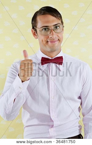 Portrait of young male geek gesturing thumbs up over yellow textured background