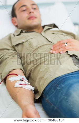 Male transfused lying on a bed in hospital ward