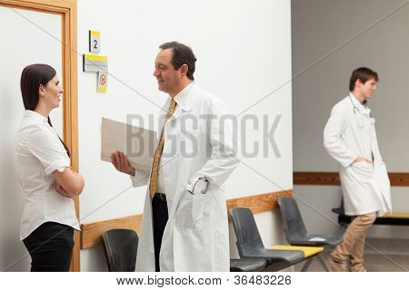 Doctors and a patient talking in an hospital hallway