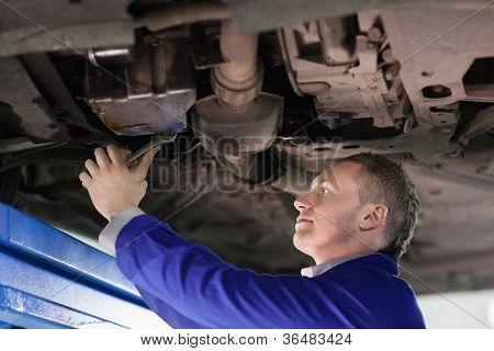 Mechanic repairing the below of a car in a garage