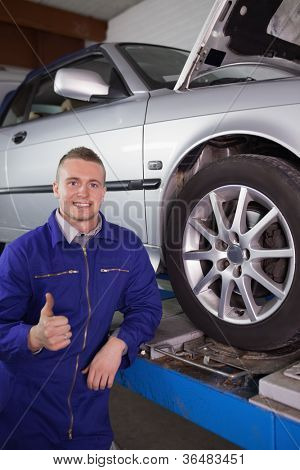 Man smiling next to a car with his thumb up in a garage