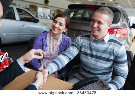 Happy couple shaking the hand of a salesman while receiving car keys