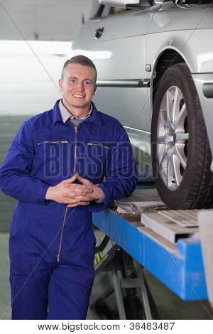 Front view of a smiling mechanic next to a car in a garage