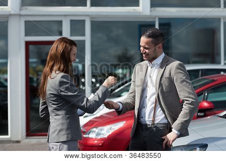 Businesswoman giving car keys to a man in a garage