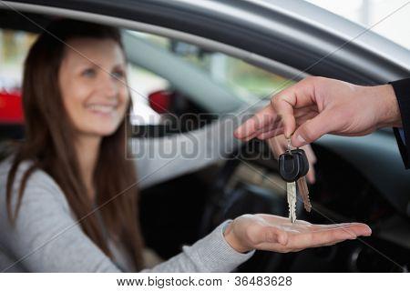 Happy woman receiving car keys in a garage