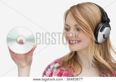 Woman holding a cd while looking it against a white background
