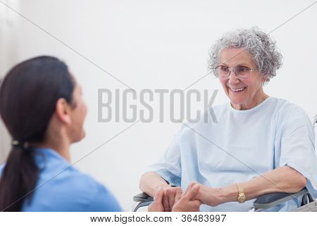 Nurse holding hands of a patient in hospital ward