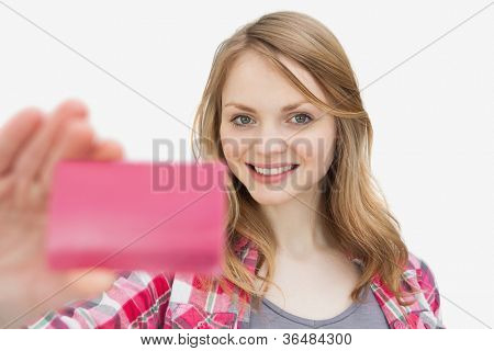 Woman holding a loyalty card while looking at camera against a white background