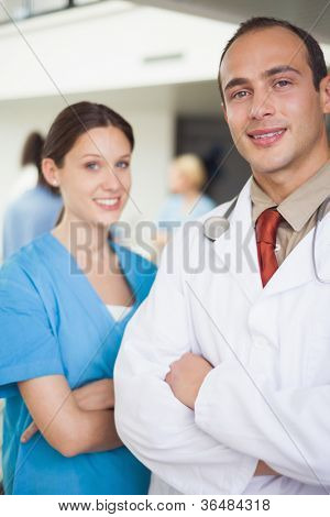 Doctor and nurse with arms crossed in hospital ward