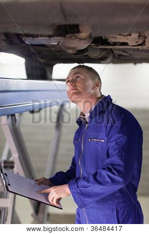 Mechanic looking at the below of a car in a garage