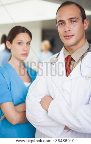 Serious doctor and nurse with arms crossed in hospital ward
