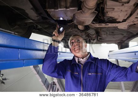 Smiling mechanic illuminating a car with a flashlight in a garage