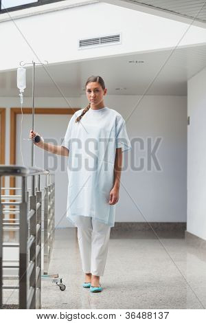 Patient walking with a drip stand in hospital hallway