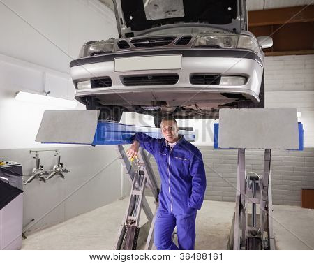 Man leaning on a machine in a garage