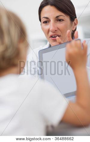 Doctor mostrando un equipo tablet PC a un niño en la sala de examen
