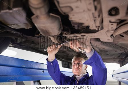 Mechanic using tools in a garage