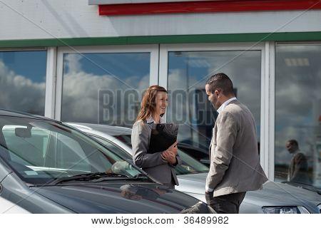 Businesswoman speaking  to a man in a garage