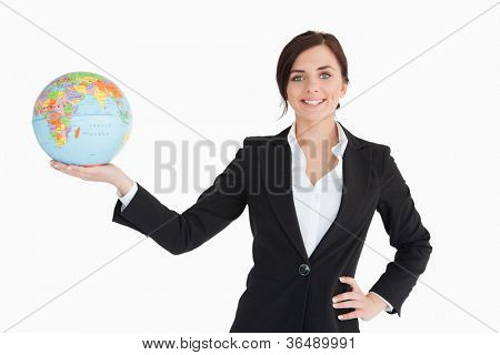 Smiling businesswoman holding an earth globe in her palm against white background