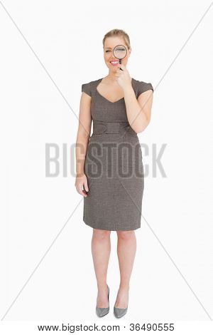 Woman holding a magnifying glass in front of her eye against white background