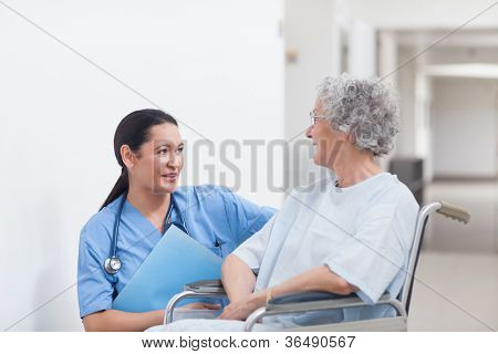 Nurse next to a patient in a wheelchair in hospital ward
