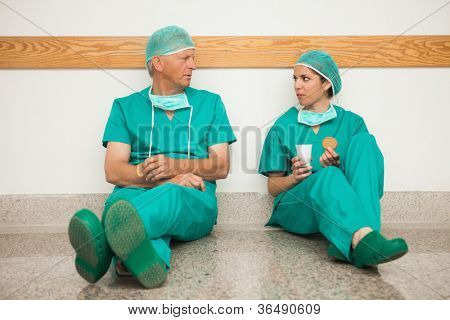 Surgeons having a break in the corridor in a hospital