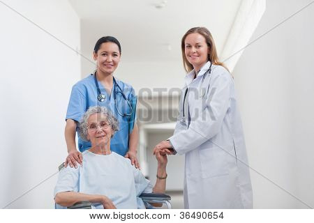 Patient in corridor holding hand of a doctor in hospital ward