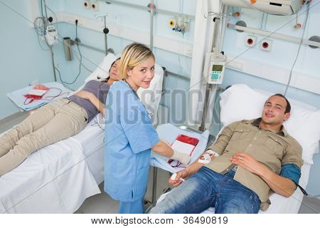 Transfused patients and a nurse looking at camera in hospital ward