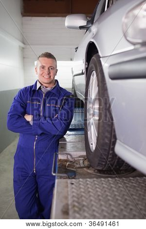 Front view of a mechanic smiling next to a car in a garage